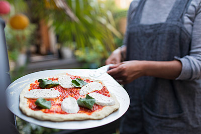 Woman with fresh homemade margherita pizza on peel - p1023m2208354 by Sam Edwards