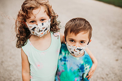 Close up of two young kids outside wearing homemade masks - p1166m2201620 by Cavan Images
