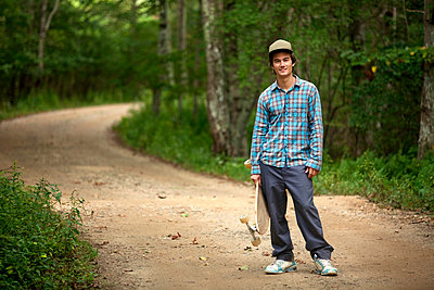Portrait of man with skateboard standing on dirt road in forest - p1166m985468f by Cavan Images