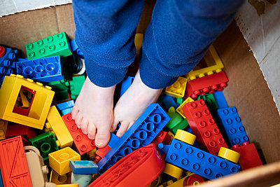Detail shot of a girl with her feet in a box of toy blocks - p1480m2148173 by Brian W. Downs