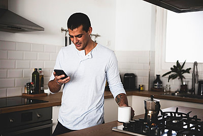 Smiling young man with cup of coffee using cell phone in kitchen at home - p300m2069671 von Eloisa Ramos