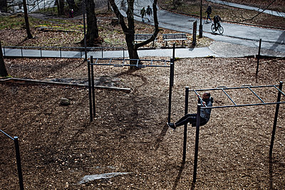 High angle view of male athlete hanging from monkey bars in forest - p426m1468542 by Maskot