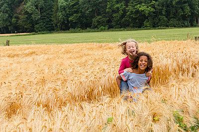 Kinder spielen auf Feld mit Gerste - p471m2022070 von CLMasur