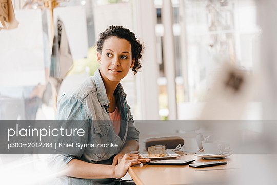 Young woman working in coworking space, eating cake - p300m2012764 von Kniel Synnatzschke
