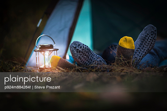 Couple lying in tent -  feet together - p924m884284f by Steve Prezant