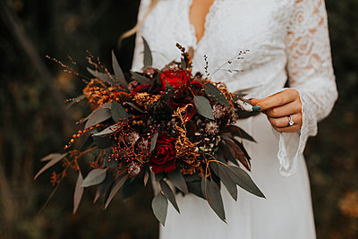 Mid section of bride holding wedding bouquet - p312m2249768 by Jennifer Nilsson