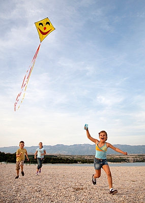 Children flying kite at beach - p42910677f by Henglein and Steets