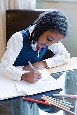 Black girl wearing school uniform doing homework - p555m1304046 by Alexander Robinson