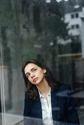 Geschäftsfrau blickt aus dem Fenster - p586m1510780 von Kniel Synnatzschke