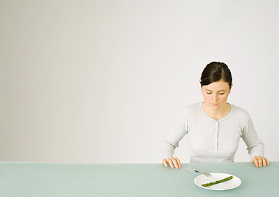 Young woman looking down at single asparagus on plate - p62316816f by Matthieu Spohn