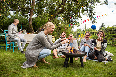 Friends roasting marshmallows in the allotment garden - p788m1165256 by Lisa Krechting