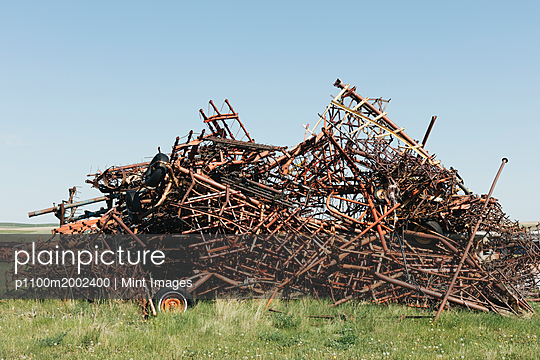 Pile of discarded farming equipment in rural landfill, near Kildeer, Saskatchewan, Canada. - p1100m2002400 by Mint Images