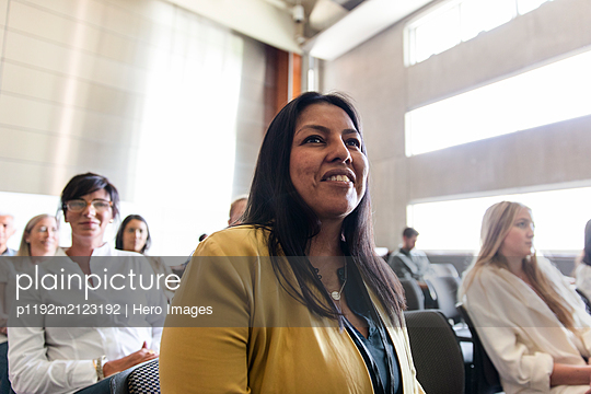 Smiling businesswoman listening in conference audience - p1192m2123192 by Hero Images