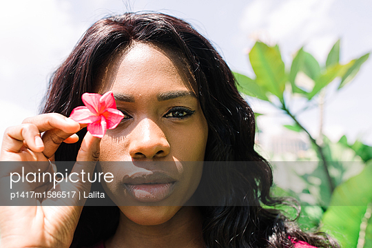 Beautiful Young Woman Holding a Pink Flower Over Her Eye - p1417m1586517 by Jessica Lia