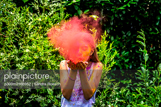 Girl blowing red powder paint in nature - p300m2166952 by Sandra Roesch