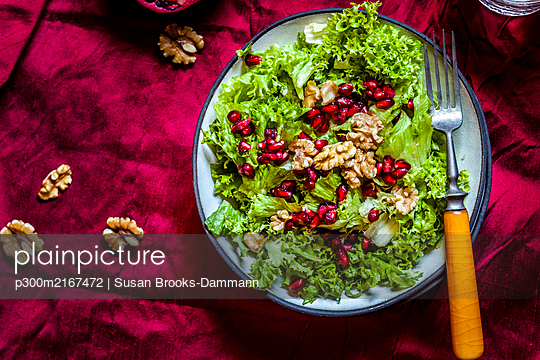 Bowl of green salad with walnuts and pomegranate seed - p300m2167472 by Susan Brooks-Dammann