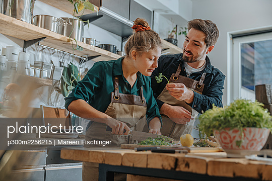 Young chef smelling parsley while cutting scallions standing by colleague on kitchen island - p300m2256215 by Mareen Fischinger