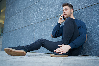 Side view of modern male in casual wear sitting near stone wall and br - p1166m2171494 by Cavan Images