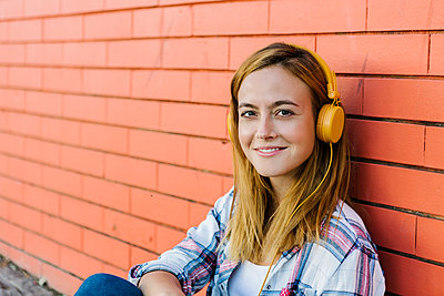 Smiling woman listening music through headphone sitting against brick wall - p300m2226716 by Xavier Lorenzo