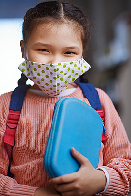 Girl with protective face mask holding pencil case during pandemic - p300m2273700 by Arman Zhenikeyev