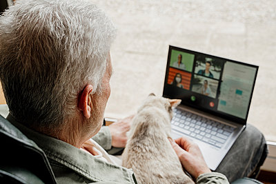 Senior man with cat on video call through laptop at home - p300m2281367 by VITTA GALLERY