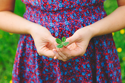 Finland, Helsinki, Aggelby, Mid section shot of woman holding four-leaf clover - p352m1127412f by Eija Huhtikorpi