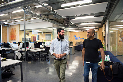 Colleagues walking through office chatting - p429m1513848 by G. Mazzarini