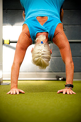 Older woman doing handstand in gymnasium - p555m1303549 by Stephen Simpson Inc
