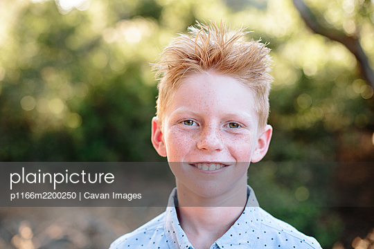 Portrait Outside Of A Red Haired Boy With Freckles - p1166m2200250 by Cavan Images