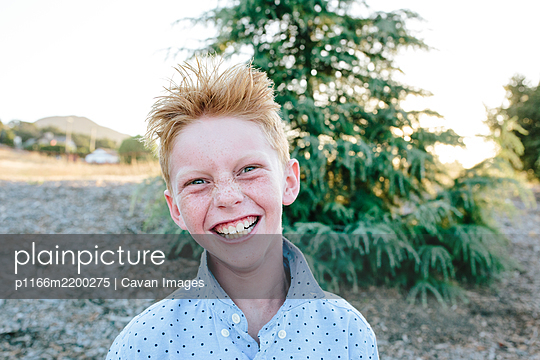 A Red Headed Boy With Freckles Smiling A Crazy Smile - p1166m2200275 by Cavan Images