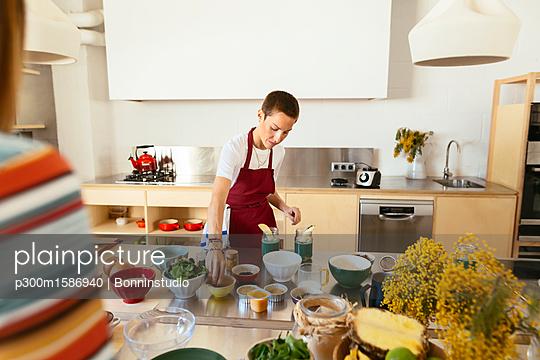 Woman preparing food in kitchen - p300m1586940 von Bonninstudio