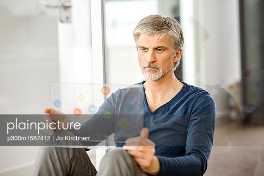 Mature businessman using transparent touchscreen computer - p300m1587412 von Jo Kirchherr