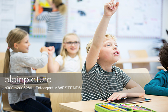 Schoolboy with tablet raising his hand in class - p300m2005286 by Fotoagentur WESTEND61