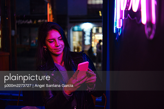 Smiling woman using mobile phone in city - p300m2273727 by Angel Santana Garcia