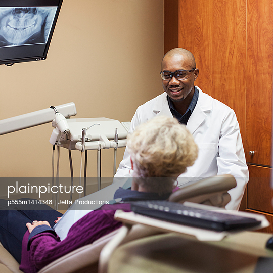 Dentist talking to patient in office