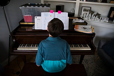 Rear View of Tween Boy Playing Piano at Home From Marked Pages in Book - p1166m2189824 by Cavan Images