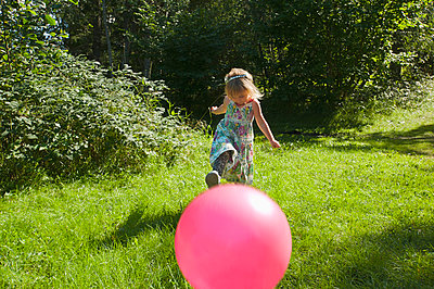 Little girl kicking a red ball - p1418m2007542 by Jan Håkan Dahlström