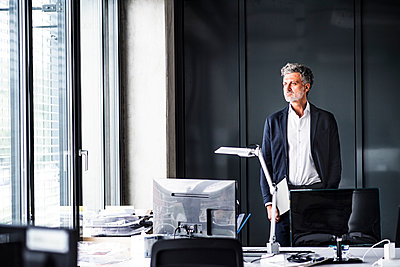 Mature businessman standing in office loooking out of window - p300m1535590 by HalfPoint