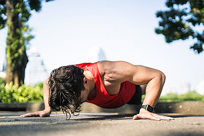 Athlete doing push-ups in urban park - p300m1550230 by Steve Brookland