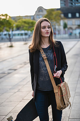 Young woman with longboard and cell phone in the city on the move - p300m2059403 by Uwe Umstätter