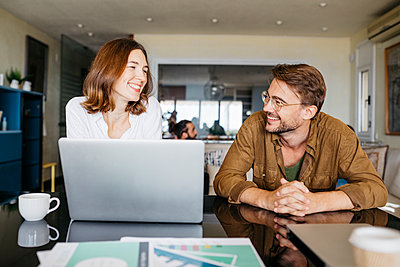 Happy man and woman working together with laptop on table at home - p300m2143887 by Josep Rovirosa