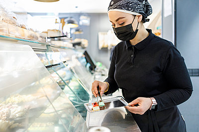 Female owner with cake on tray at display cabinet in bakery - p300m2281883 by Ignacio Ferrándiz Roig