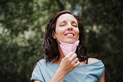 Smiling woman eyes closed removing protective face mask in forest - p300m2293408 by Eva Blanco