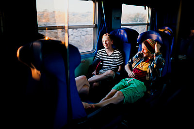 Smiling couple sitting in train - p312m2080052 by Matilda Holmqvist