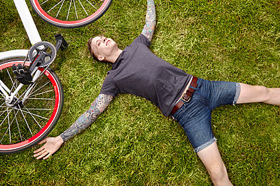 Young tattooed man lying on grass - p429m802536 by Cultura