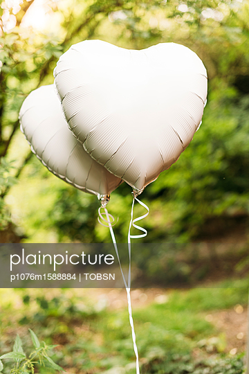 Herzförmige Luftballons vor grünem Hintergrund - p1076m1588884 von TOBSN