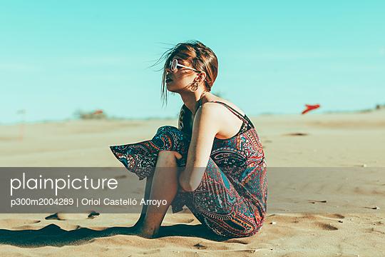 Young woman sitting in desert landscape - p300m2004289 von Oriol Castelló Arroyo