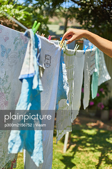 Man hanging up laundry outdoors - p300m2156752 by Veam
