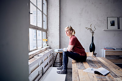 Smiling woman with coffee mug sitting on desk in loft looking through window - p300m2030229 by Rainer Berg
