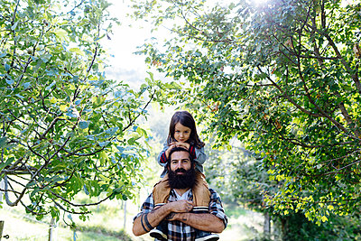 Portrait of father with kid on his shoulders in an orchard - p300m2144756 by Sofie Delauw